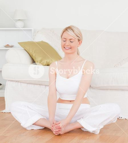 Young smiling female doing relaxation exercises while sitting on the floor