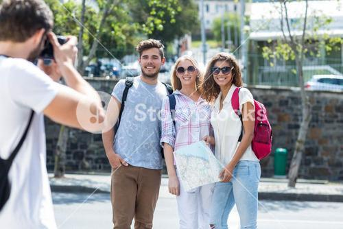 Hip man taking picture of his friends