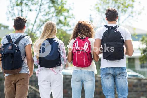 Rear view of hip friends with backpacks