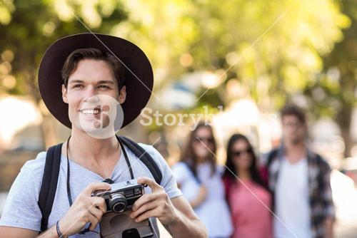 Hip man with digital camera smiling