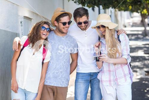 Hip friends looking at smartphone