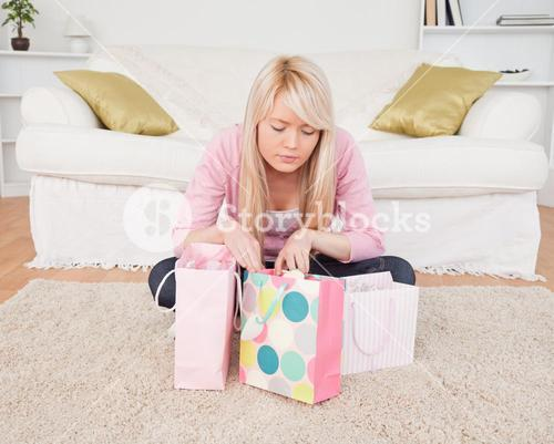 Blonde woman sitting in the livingroom with her shopping bags