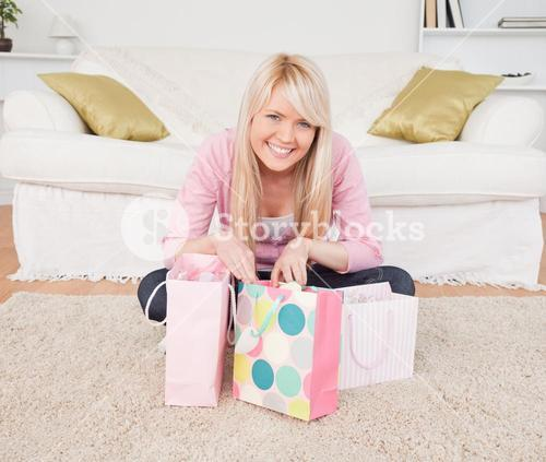 Smiling blonde woman sitting in the livingroom with her shopping bags