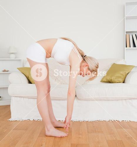 Good looking blonde female stretching in the living room