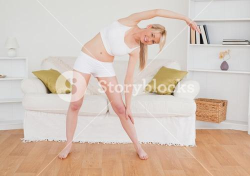 Pretty blonde woman stretching in the living room