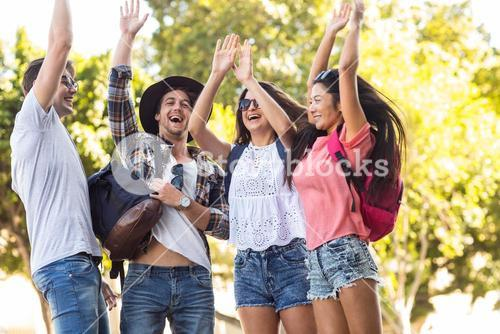Hip friends cheering up with arms raised