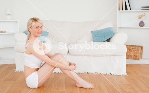 Beautiful female in underwear posing while sitting on the floor
