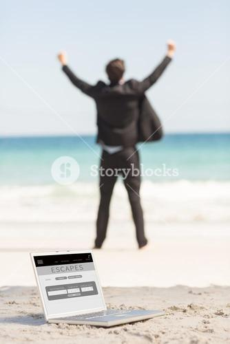 Composite image of happy businessman cheering in front of the sea