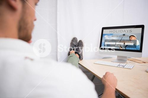 Composite image of businessman with legs crossed at ankle on office desk