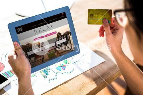 Composite image of cropped image of hipster businessman using tablet and credit card