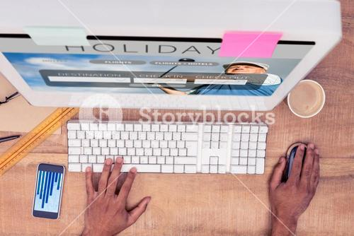 Composite image of businessman using computer while working at desk