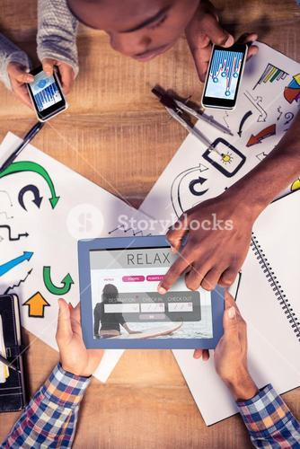 Composite image of overhead view of creative team working at desk
