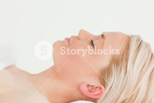 Attractive blondhaired woman relaxing while lying down