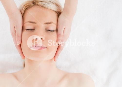 Delighted blondhaired woman getting a massage on her face