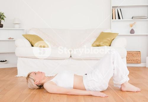 Delighted blondhaired woman doing fitness exercises