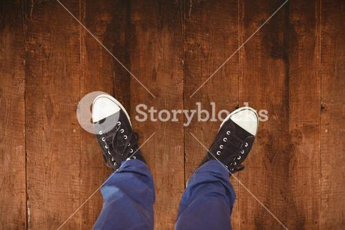 Composite image of man standing on hardwood floor