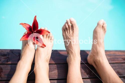 Couple bare feet against swimming pool