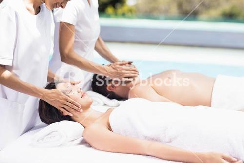 Couple receiving a face massage from masseur