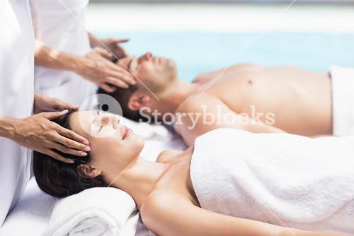 Couple receiving a head massage from masseur