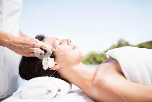 Woman receiving a head massage from masseur