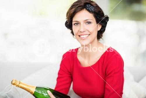 Portrait of beautiful woman holding champagne bottle