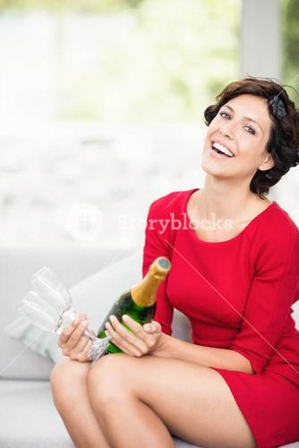Portrait of beautiful woman holding champagne bottle and glass