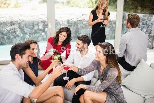 Group of friends toasting cocktail drinks