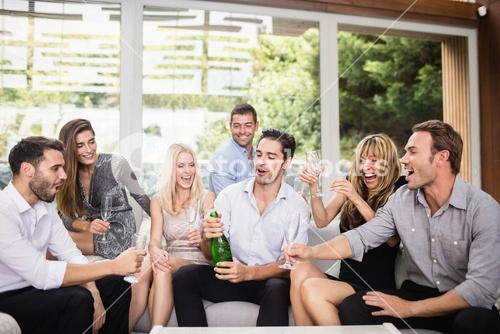 Man popping champagne bottle with friends