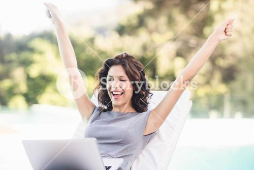 Excited young woman using laptop near poolside