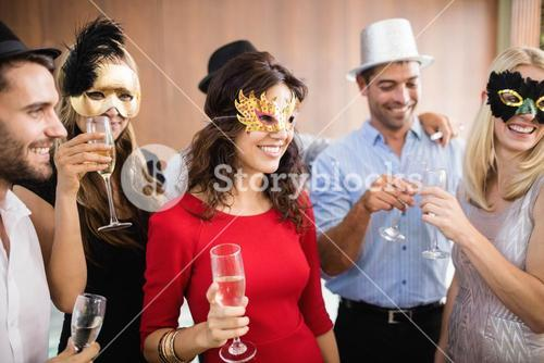Friends with masks on holding champagne glasses