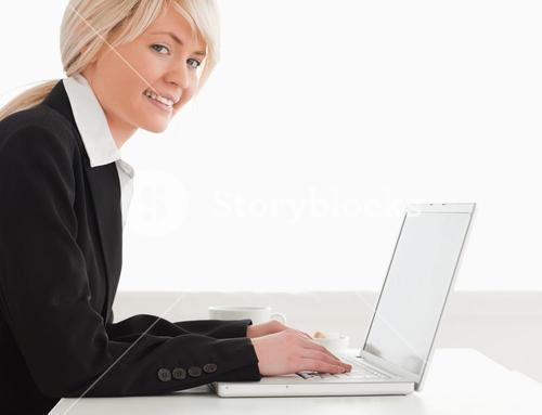 Professional woman posing while relaxing on a laptop