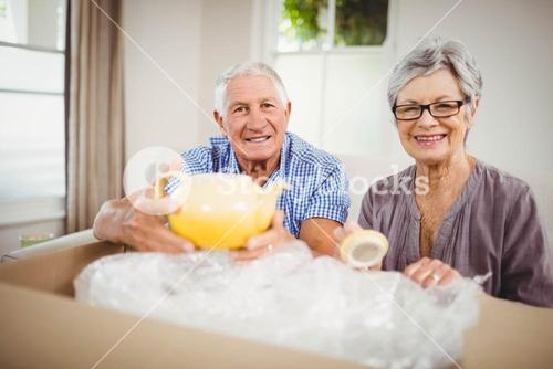 Senior couple unpacking a cardboard box