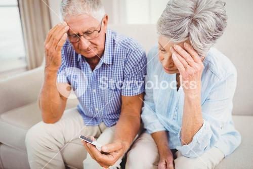 Sad senior couple looking at mobile phone