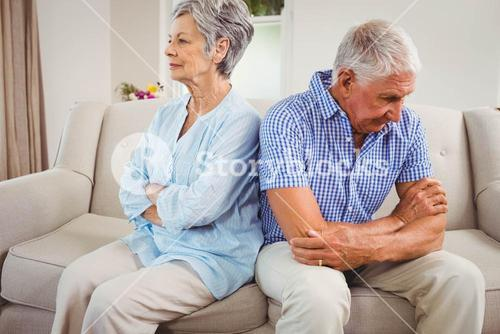 Sad senior couple sitting on sofa