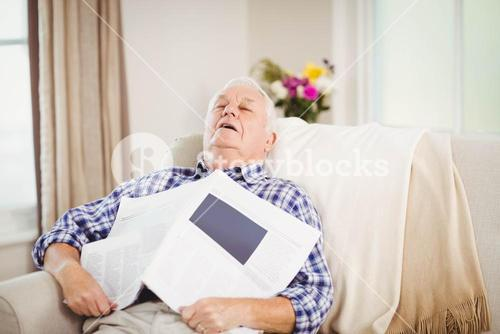 Senior man relaxing on sofa with newspaper