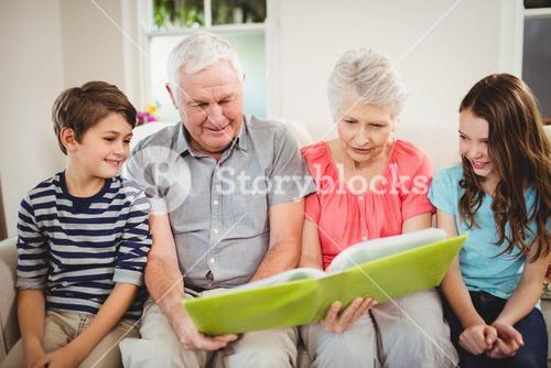 Senior couple reading a book with their grand children