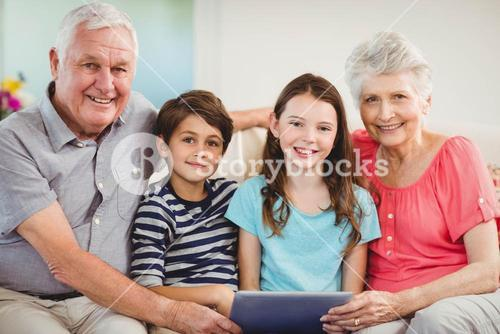 Senior couple using digital tablet with their grand children