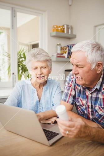 Senior couple holding a pill bottle while operating laptop