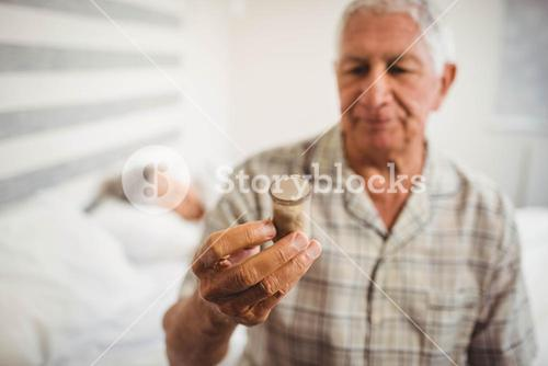 Senior man looking at a pill bottle