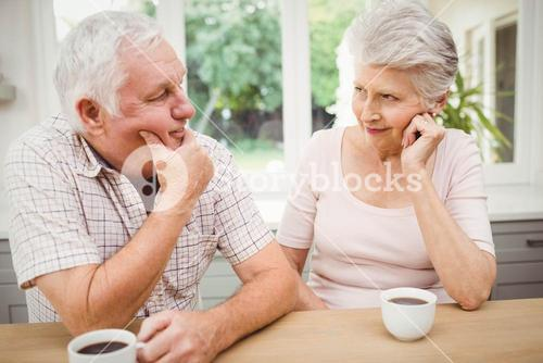 Senior couple talking to each other while having coffee