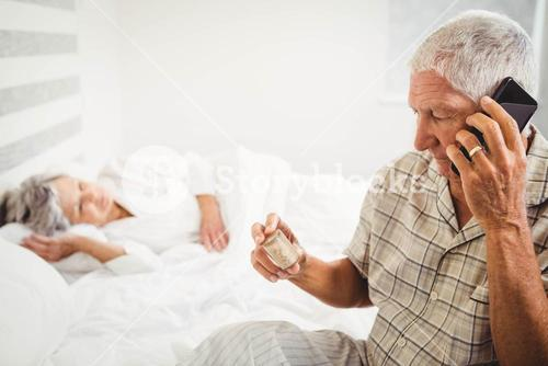 Senior man looking at pill bottle and talking on phone