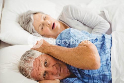 Senior man covering her ears while man snoring