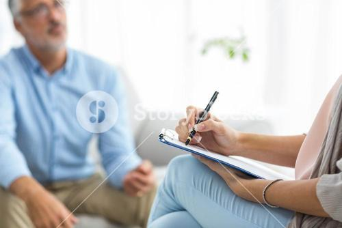 Female doctor writing on clipboard while consulting a man