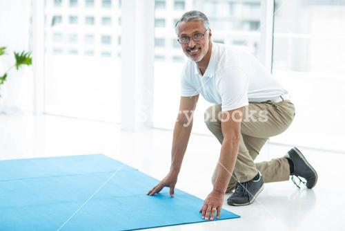 Physiotherapist laying exercise mat