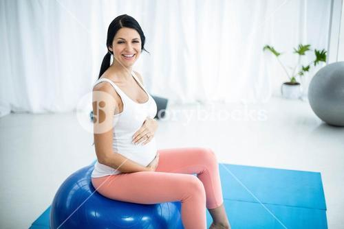 Pregnant woman exercising on exercise ball