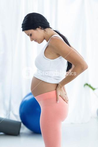 Pregnant woman looking down while exercise