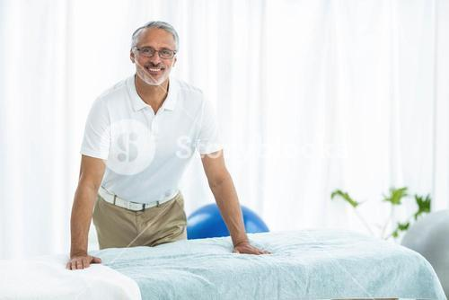 Physiotherapist standing near massage table
