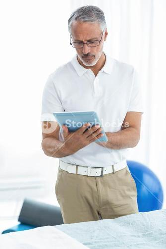 Physiotherapist using digital tablet