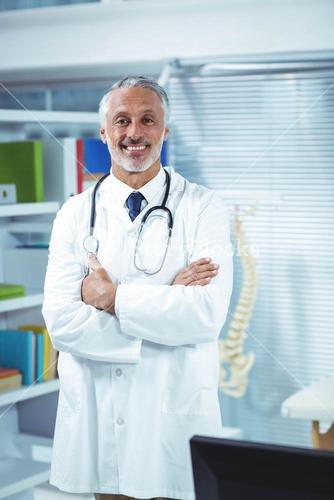 Doctor standing with arms crossed in clinic