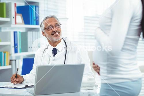 Pregnant woman with doctor at clinic